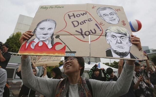 פעילים ירוקים בקוריאה הדרומית עם כרזה שבה גרטה ת'ונברג נוזפת בטראמפ, 2019 (צילום: AP Photo/Ahn Young-joon)