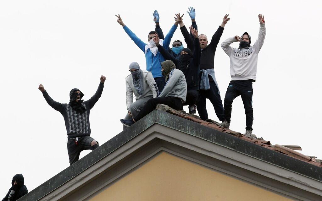 אסירים באיטליה עולים על הגג במחאה על החוקים החדשים שנועדו לעצור את התפשטות הקורונה, מרץ 2020 (צילום: AP Photo/Antonio Calanni)