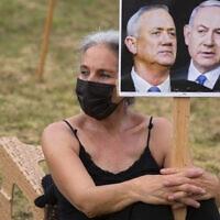 מפגינה נגד ממשלת האחדות של הליכוד וכחול לבן מחזיקה בשלט עם תמונות של בנימין נתניהו ובני גנץ, 14 במאי 2020 (צילום: AP Photo/Sebastian Scheiner)