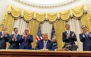 """נשיא ארה""""ב דונלד טראמפ מכריז על הסכם נירמול היחסים בין ישראל ואיחוד האמירויות. מאחוריו, משמאל: בריאן הוק, אבי ברקוביץ, דיוויד פרידמן, ג'ארד קושנר וסטיב מנושין. 12 באוגוסט 2020 (צילום: AP Photo/Andrew Harnik)"""