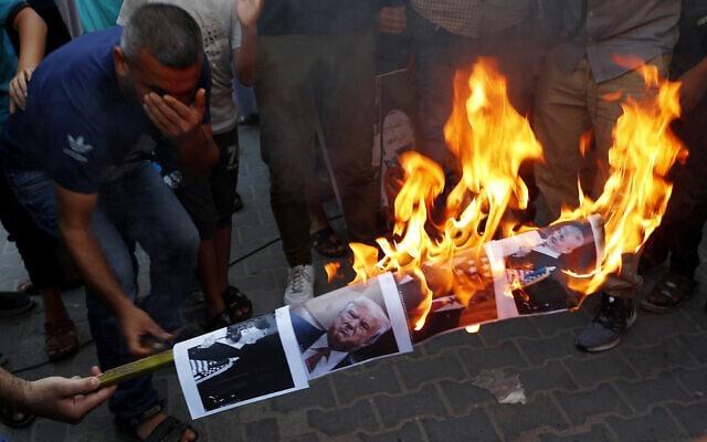 פלסטינים שורפים בג'באליה שברצועת עזה את תמונותיהם של ראש ממשלת ישראל בנימין נתניהו ושל נשיא ארצות הברית דונלד טראמפ במחאה על ההסכם לכינון יחסים עם איחוד האמירויות, 15 באוגוסט 2020 (צילום: Adel Hana, AP)