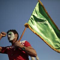 תומך של המורדים החות'ים, אוחז בדגל ירוק לאות תמיכה בהם בצנעא, תימן, אוקטובר 2020 (צילום: AP Photo/Hani Mohammed)