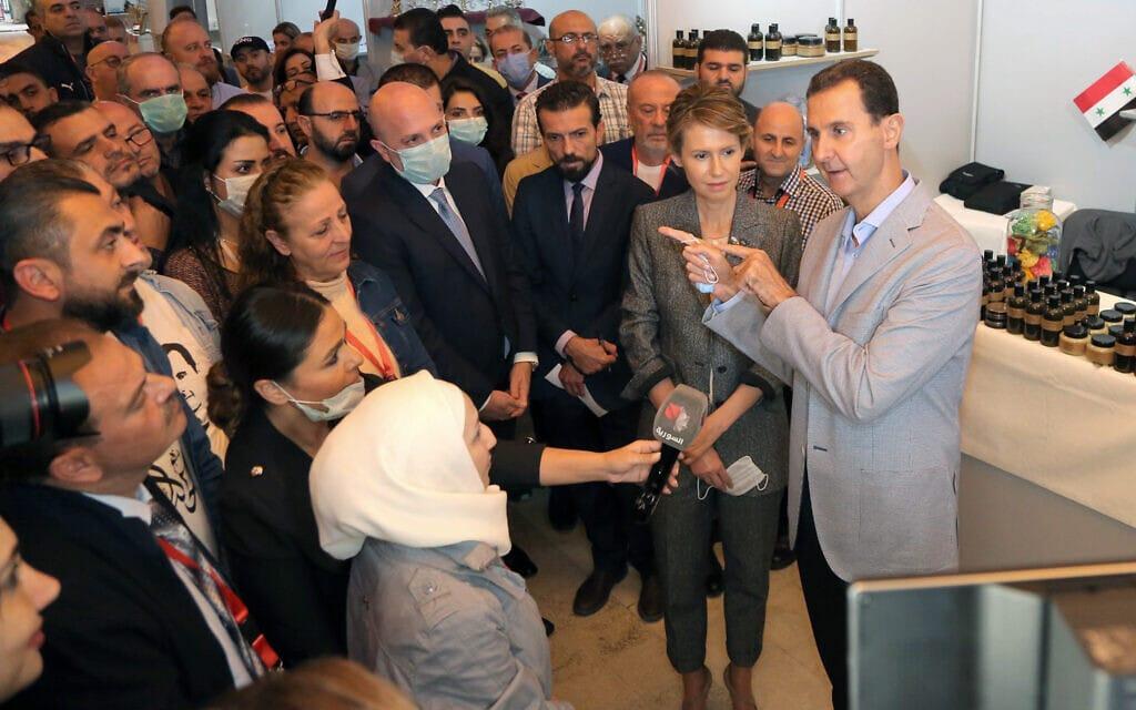 בתצלום, שסופק על ידי עמוד הפייסבוק של נשיאות סוריה, אסד ואשתו אסמה מדבר עם אנשים במהלך ביקור בתערוכה בדמשק, נובמבר 2020 (צילום: Syrian Presidency Facebook page via AP)