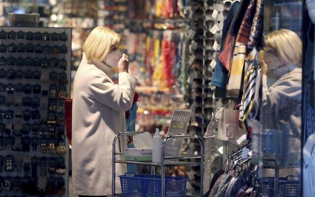 אישה לובשת מסכה בחנות בווינה, אוסטריה. הממשלה אוסטריה הגבילה את חופש התנועה מ-17 בנובמבר (צילום: AP Photo/Ronald Zak)
