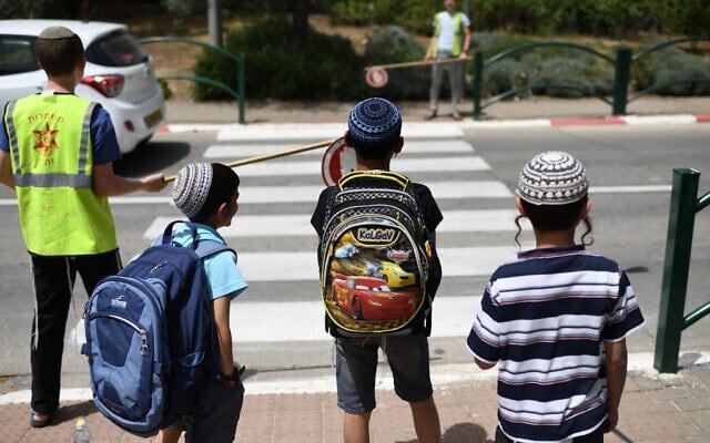 תלמידי בית ספר חוצים כביש בעזרת משמרות הזה״ב (צילום: Gili Yaari /Flash90)