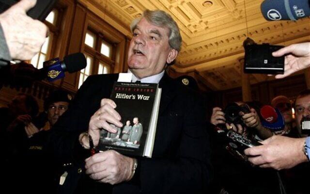 """מכחיש השואה דייוויד אירווינג אוחז בספרו """"מלחמת היטלר"""" בבית משפט בווינה, 20 בפברואר 2006 (צילום: Hans Punz, AP)"""