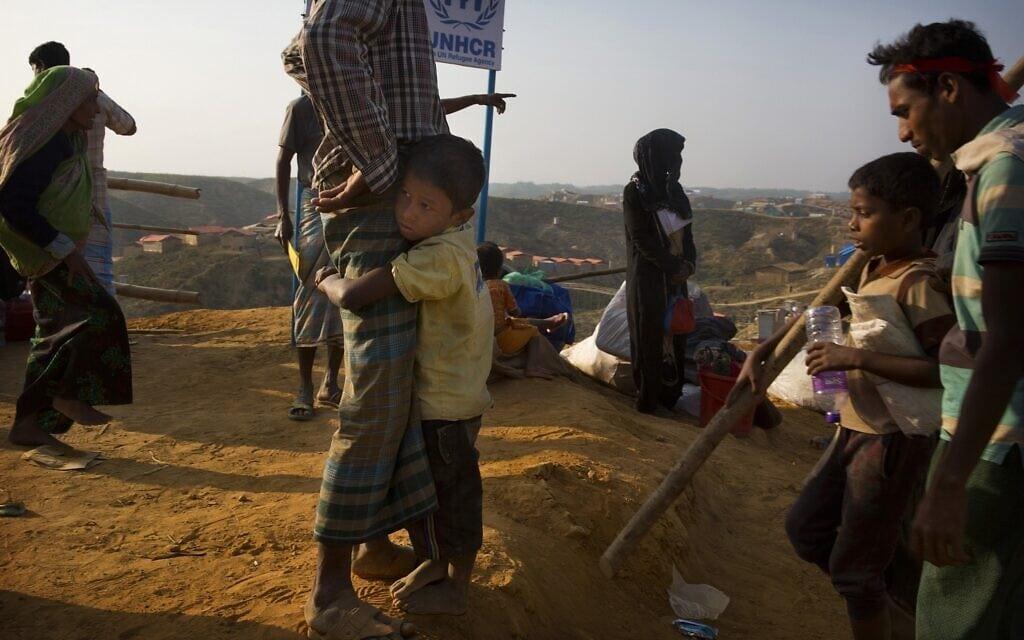 """ילד פליט רוהינגי ששהה בשטח הפקר בבנדרבן, בין מיאנמר לגבול בנגלדש, נצמד לאביו עם הגיעם למחנה הפליטים בלוחאלי, 50 ק""""מ מקוקס באזר, בנגלדש, 24 בינואר 2018 (צילום: צילום: AP Photo/Manish Swarup)"""