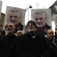 מפגינים נושאים שלטים ובהם תמונה של קאסם סלימאני, מפקד משמר המהפכה האיראני, שחוסל בהתקפה אמריקאית בנמל בגדד ב-2020 (צילום: AP Photo/Lefteris Pitarakis)