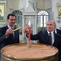 נשיא רוסיה ולדימיר פוטין ונשיא סוריה בשאר אסד מדליקים נרות בקתדרלה הנוצרית האורתודוקסית בדמשק, 7 בינואר 2020 (צילום: Alexei Druzhinin, Sputnik, Kremlin Pool Photo via AP)