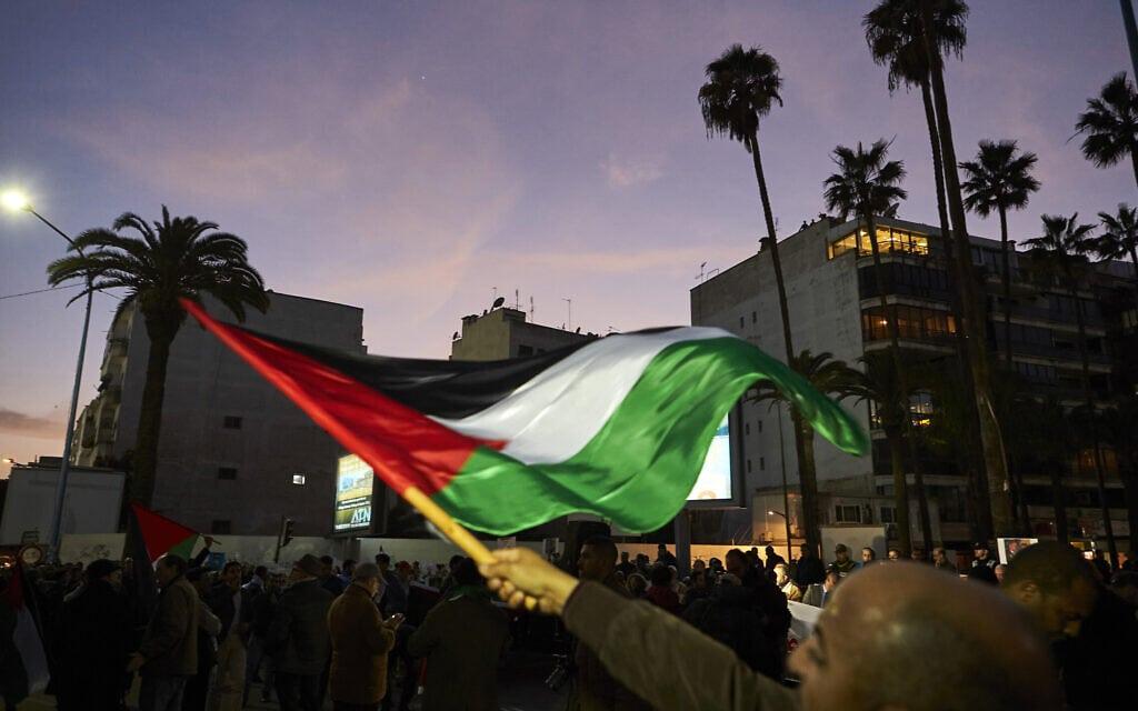 אדם בקזבלנקה מנופף בדגל פלסטין במהלך מחאה נגד תוכנית השלום האמריקנית במזרח התיכון. מרוקו ינואר 2020 (צילום: AP Photo/Abdeljalil Bounhar)