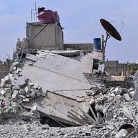 בתמונה שהוציאה סוכנות הידיעות הרשמית של סוריה, נראה בניין הרוס בפרברי דמשק, אשר לטענת הסורים נפגע בהתקפת חיל האוויר הישראלי. 27 באפריל 2020 (צילום: SANA via AP)