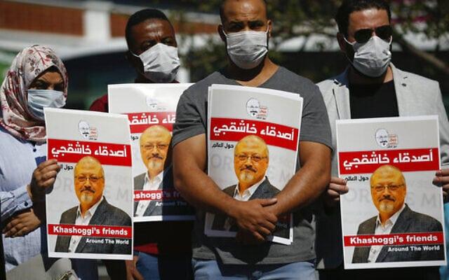אנשים נושאים את תמונתו של ג'מאל ח'אשוקג'י ליד הקונסוליה הסעודית באיסטנבול לציון שנתיים למותו, 2 באוקטובר 2020 (צילום: Emrah Gurel, AP)