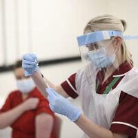 אחות מכינה חיסון נגד קורונה לאדם הראשון בצפון אירלנד שקיבל את החיסון של חברת פייזר. דצמבר 2020 (צילום: Liam McBurney/Pool via AP)