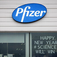 """""""שנה טובה, המדע ינצח"""" – כיתוב על חלון משרדי חברת פייזר בבלגיה, 21 בדצמבר 2020 (צילום: AP Photo/Valentin Bianchi)"""