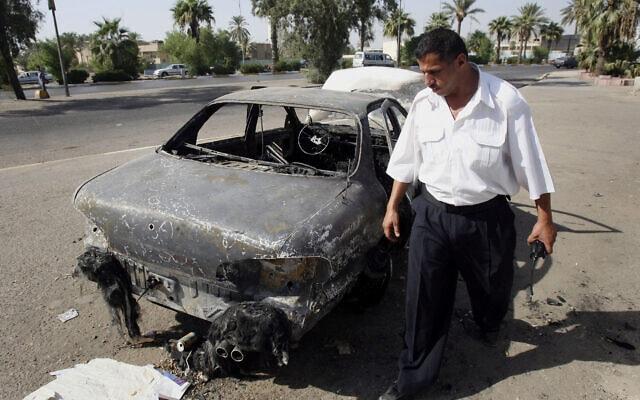 """שוטר בוחן מכונית שנפגעה מהירי של אנשי חברת """"בלאקווטר"""" בבגדאד, 25 בספטמבר 2007 (צילום: Khalid Mohammed, AP)"""