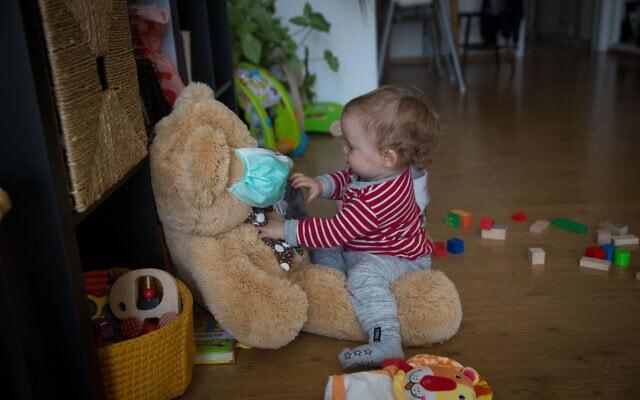 אילוסטרציה. תינוקת משחקת בביתה עם בובת דוב במסיכה (צילום: Miriam Alster/Flash90)