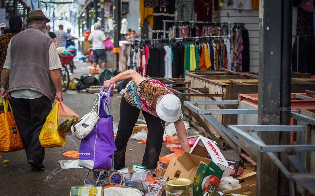 אישה מלקטת מהרצפה פירות וירקות שהושלכו בשוק. יולי 2020 (צילום: Yossi Aloni/Flash90)