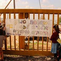 שער היישוב בת עין עליו שלט שהכינו נערות לאחר מותו של אהוביה סנדק (צילום: Gershon Elinson/Flash90)