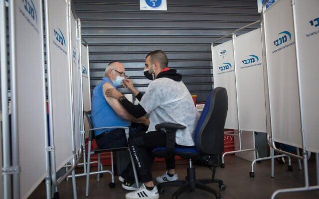 מטופל מקבל את המנה הראשונה מתוך שתיים של החיסון נגד קורונה, במרכז של קופת החולים מכבי בתל אביב. 22 בדצמבר 2020 (צילום: מרים אלסטר, פלאש 90)