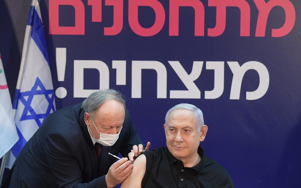 """ראש הממשלה בנימין נתניהו מקבל את החיסון הראשון לנגיף הקורונה בבית החולים שיבא, 19 בדצמבר 2020 (צילום: עמוס בן גרשום/לע""""מ)"""