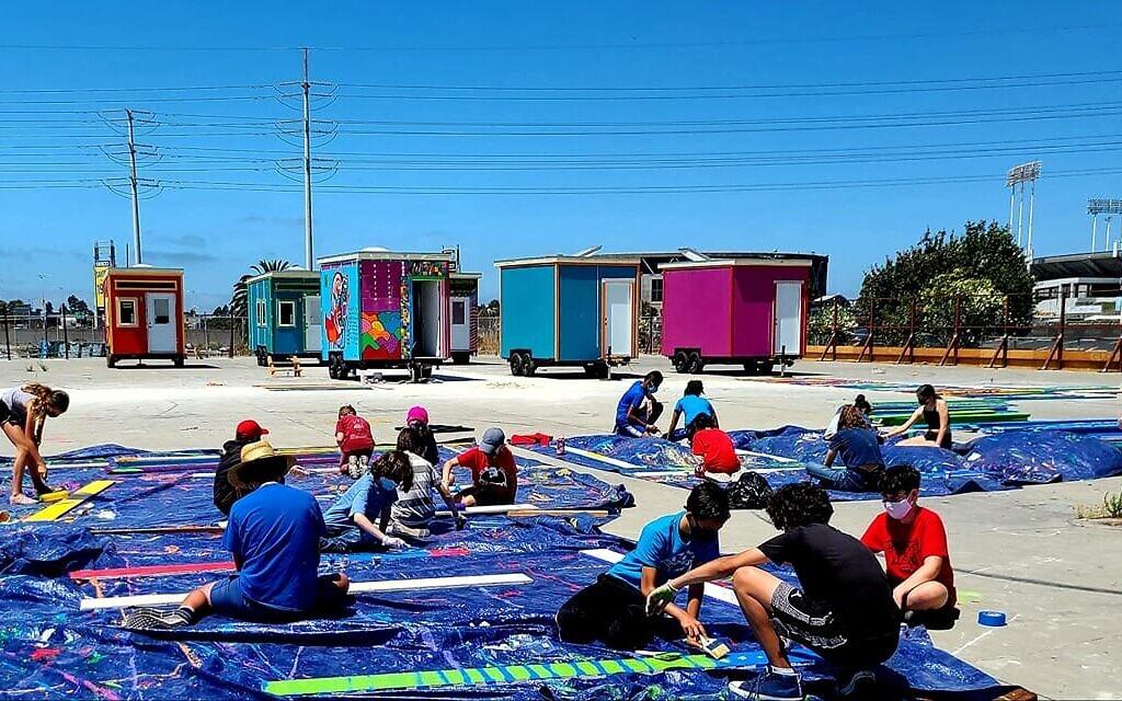 """משתתפי מחנה הקיץ """"כי טוב"""" של קהילת בית אל צובעים לוחות עץ עבור כפר הבתים הזעירים באוקלנד, 4 באוגוסט 2020 (צילום: באדיבות סאלי הינדרמן)"""