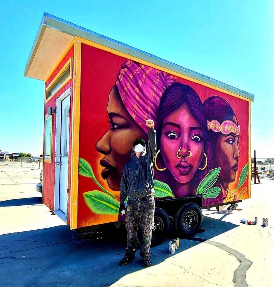האמן פנצ'ו פסקדור עומד ליד בית זעיר הנושא ציור קיר שלו, בכפר הבתים הזעירים באוקלנד, קליפורניה, ב-29 ביולי 2020 (צילום: באדיבות סאלי הינדרמן)