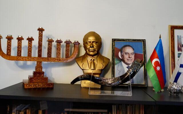 """משרד יו""""ר קהילת היהודים ההרריים של אזרבייג'ן. במשרד מוצגים חנוכייה, תמונה ופסל מוזהב של היידר אלייב, המייסד המנוח של אזרבייג'ן החדשה, דגל אזרבייג'ן ודגל ישראל (צילום: רזה/Getty Images)"""