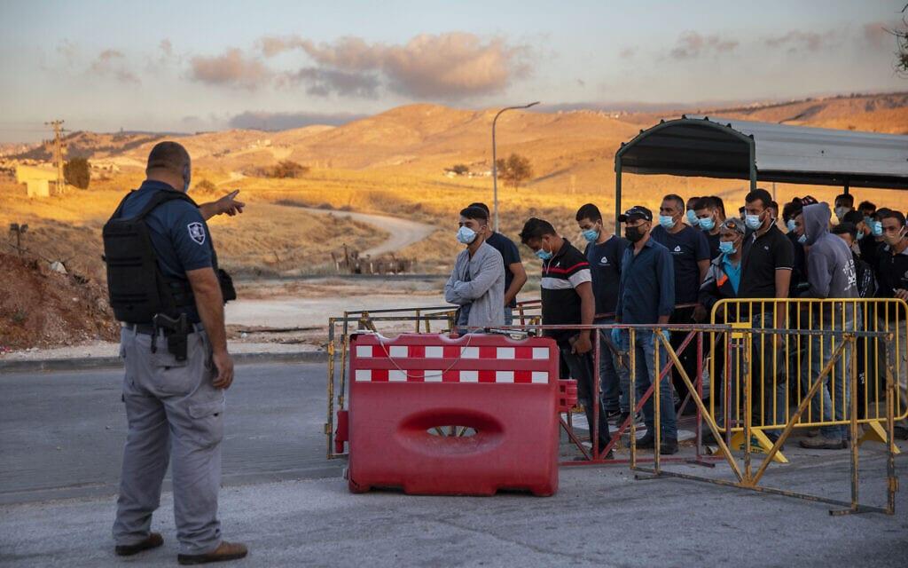עובדים פלסטינים עומדים בתור במחסום ליד מעלה אדומים ב-30 ביוני 2020 (צילום: AP Photo/Oded Balilty)