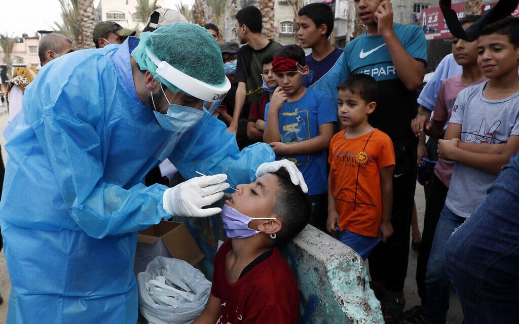 נער עובר בדיקת קורונה במחנה הפליטים ג'באליה שברצועת עזה, 30 באוקטובר 2020 (צילום: Adel Hana, AP)