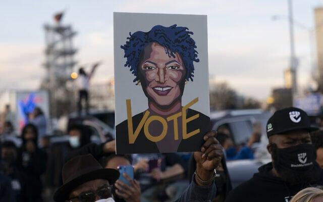 משתתפים בעצרת בחירות באטלנטה מחזיקים שלט עם תמונתה של סטייסי אברמס, ב-4 ביוני 2021 (צילום: AP Photo/Carolyn Kaster)