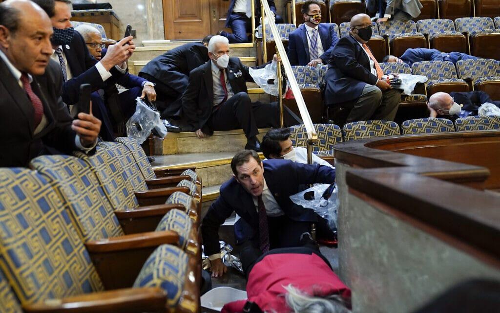 נוכחים באולם בית הנבחרים מתחבאים בין הכסאות בזמן שתומכי טראמפ פורצים לגבעת הקפיטול, 6 בינואר 2021 (צילום: AP Photo/Andrew Harnik)