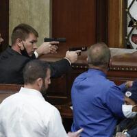 המצור על גבעת הקפיטול: שוטרים בבית הנבחרים מכוונים אקדחים לעבר מפגינים שמאיימים לפרוץ לאולם המרכזי, 6 בינואר 2021 (צילום: AP Photo/J. Scott Applewhite)