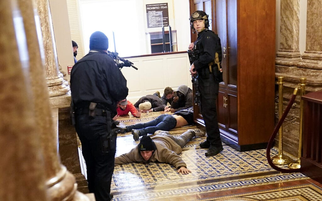 שוטרים עוצרים מפגינים שחדרו לבית הנבחרים בגבעת הקפיטול, 6 בינואר 2021 (צילום: AP Photo/Andrew Harnik)