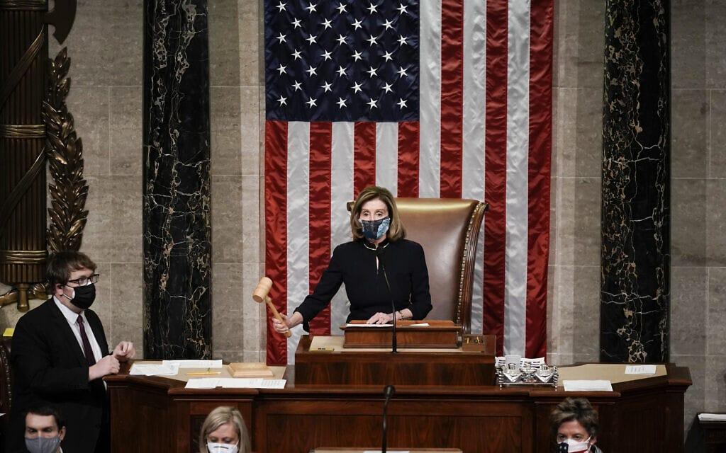 """יו""""ר בית הנבחרים ננסי פלוסי נועלת את ישיבת הקונגרס בה הוחלט להעמיד למשפט הדחה את הנשיא דונלד טראמפ, 13 בינואר 2021 (צילום: AP Photo/J. Scott Applewhite)"""