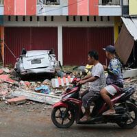 עוברי אורח חולפים על פני הנזקים שהותירה רעידת האדמה שפקדה את אינדונזיה, 15 בינואר 2021 (צילום: Sadly Ashari Said, AP)