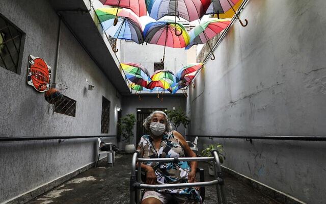 אישה ממתינה להתחסן בבית מחסה ציבורי בסאו פאולו, ברזיל. 19 בינואר 2021 (צילום: AP Photo/Marcelo Chello)