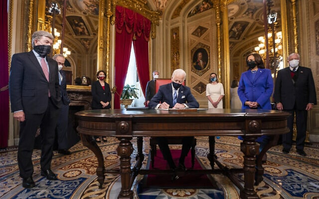 הנשיא ג'ו ביידן חותם על הצהרת השבועה עם כניסתו לתפקיד, 20 בינואר 2021 (צילום: Jim Lo Scalzo/Pool Photo via AP)
