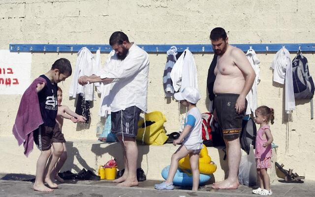 משפחה חרדית בחוף הנפרד בתל אביב (צילום: אביר סולטן/פלאש90)