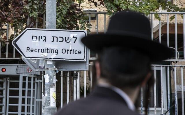 גבר חרדי חולף על פני שלט המצביע על לשכת הגיוס בירושלים, 5 בדצמבר 2019 (צילום: אוליבייה פיטוסי/פלאש90)