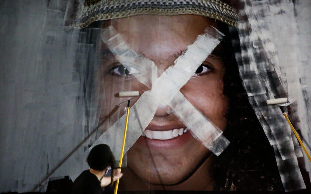 """מפגינים צובעים על תמונה של אהוביה סנדק ז""""ל במחאה נגד המשטרה שהתקיימה בכיכר רבין בתל אביב, 29 בדצמבר 2020 (צילום: מרים אלסטר/פלאש90)"""