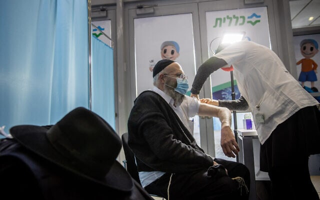 גבר חרדי מקבל חיסון נגד וירוס הקורונה בירושלים. 12 בינואר 2021 (צילום: יונתן זינדל/פלאש90)