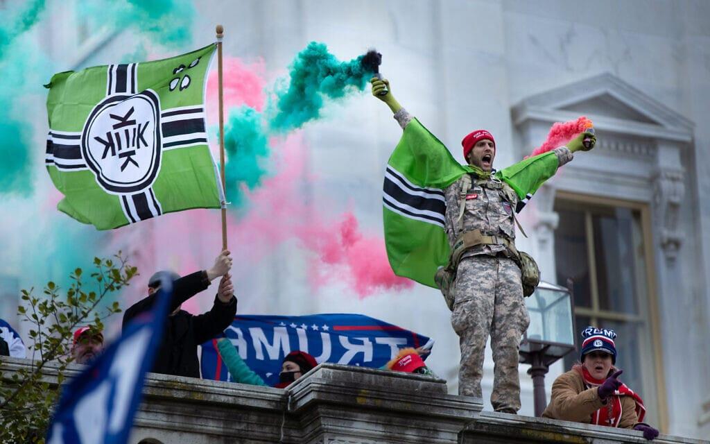 """תומכי טראמפ עם דגל ה""""קק"""" בפלישה לבית הנבחרים, 6 בינואר 2021 (צילום: Evelyn Hockstein/For The Washington Post via Getty Images/JTA)"""