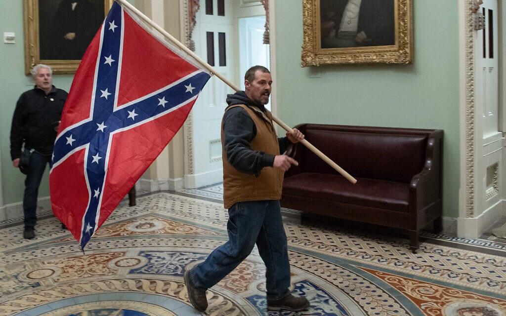 מפגין נושא את דגל הקונפדרציה בבית הנבחרים, 6 בינואר 2021 (צילום: Saul Loeb/AFP via Getty Images/JTA)