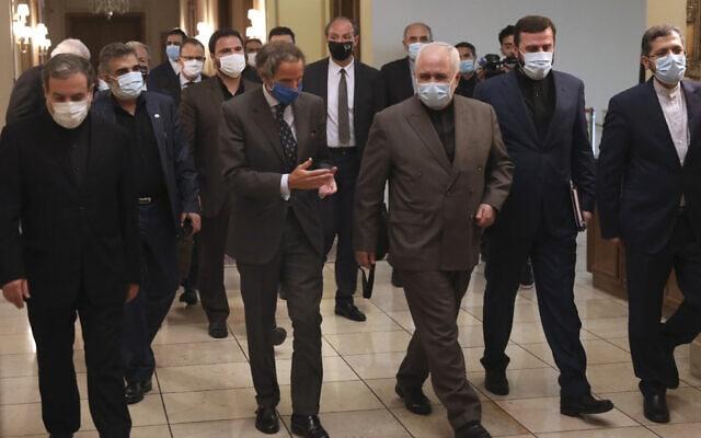 """ראש הסוכנות הבינלאומית לאנרגיה אטומית (סבא""""א), רפאל מריאנו גרוסי, במרכז-שמאל, משוחח עם שר החוץ של איראן מוחמד ג'וואד זריף, במרכז, לקראת פגישה בטרהן, 25 באוגוסט 2020 (צילום: AP Photo/Vahid Salemi)"""