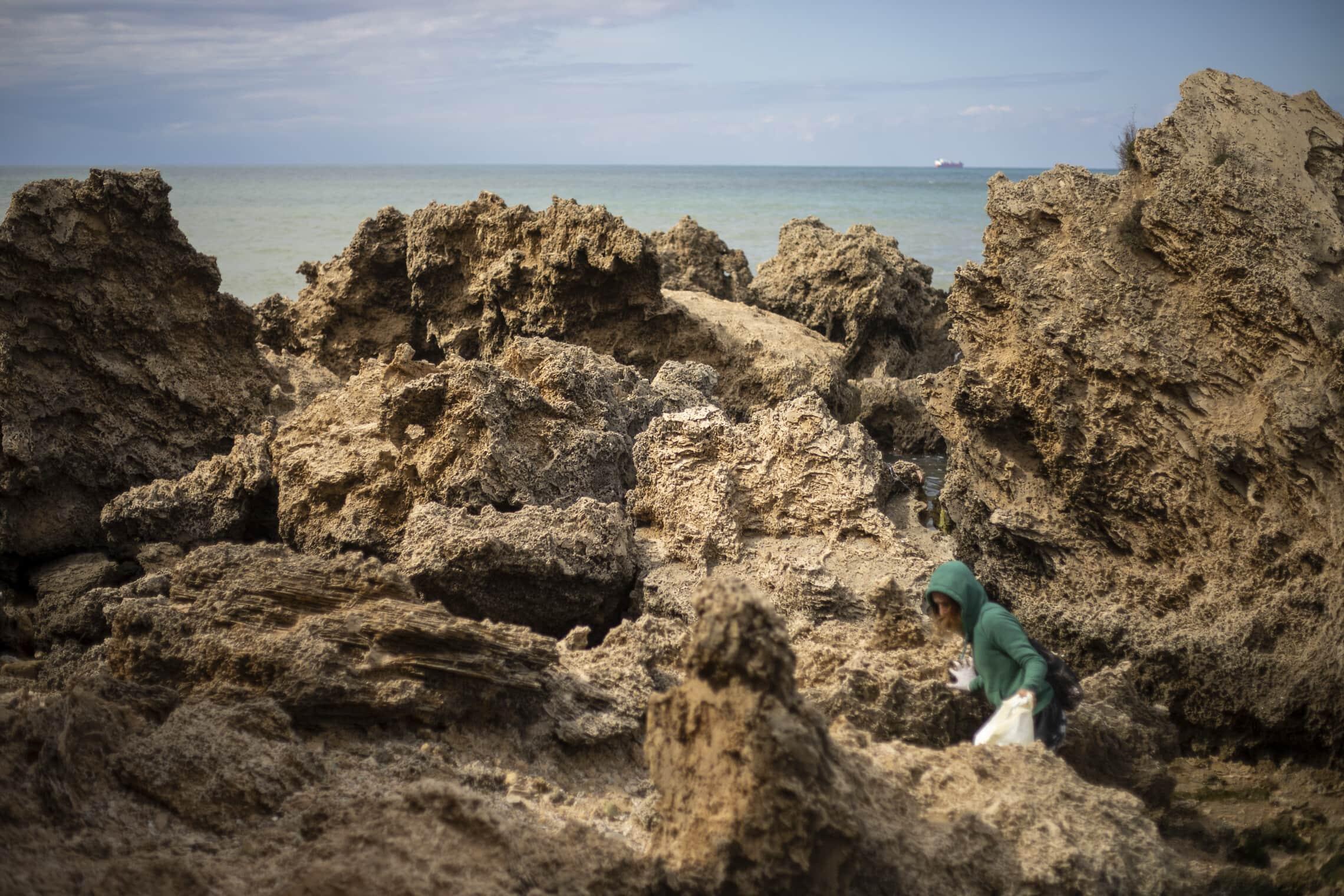 מתנדבת מנקה בחוף בעקבות דליפת הנפט שגרמה לזיהום בחופי הארץ, 20 בפברואר 2021 (צילום: AP Photo/Ariel Schalit)