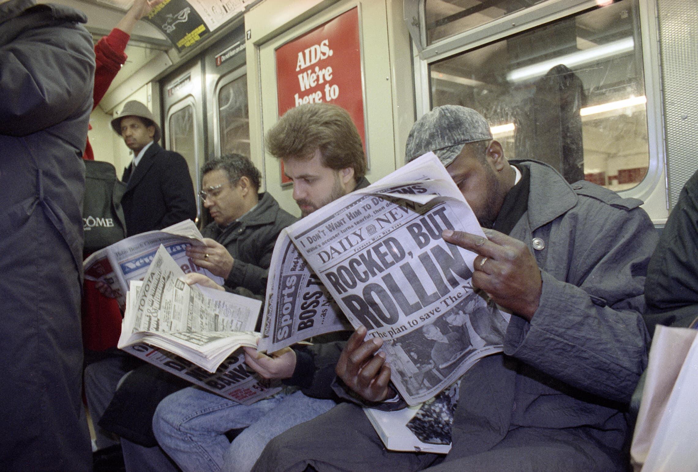 נוסעים ברכבת התחתית בניו יורק קוראים את הניו יורק דיילי ניוז ב-6 בדצמבר 1991 (צילום: AP Photo/Norman Y. Lono)