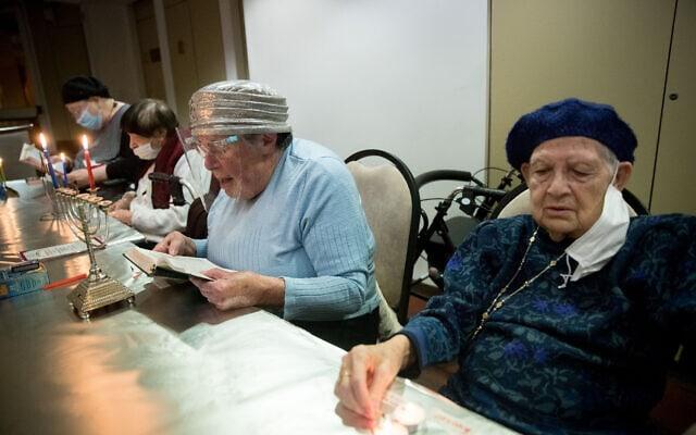 אילוסטרציה: קשישים בדיור מוגן בירושלים מדליקים נר של חנוכה, דצמבר 2020 (צילום: יונתן זינדל/פלאש90)