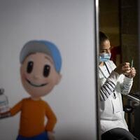 """חברת צוות רפואי מכינה חיסון קורונה במתחם קופ""""ח הכללית, אילוסטרציה (צילום: Yonatan Sindel/Flash90)"""