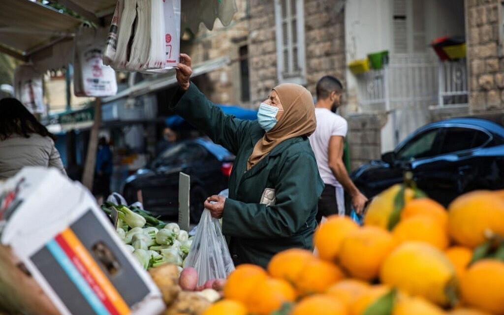 אישה עושה קניות בוואדי ניסנאס בחיפה, 5 בפברואר 2021 (צילום: Shir Torem/Flash90)