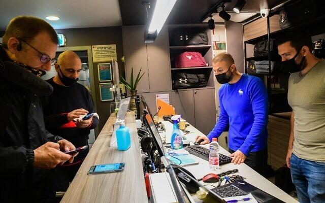 """לקוחות מציגים את התו הירוק בכניסה לחדר כושר של רשת """"הולמס פלייס"""" בתל אביב, 21 בפברואר 2021 (צילום: אבשלום ששוני/פלאש90)"""